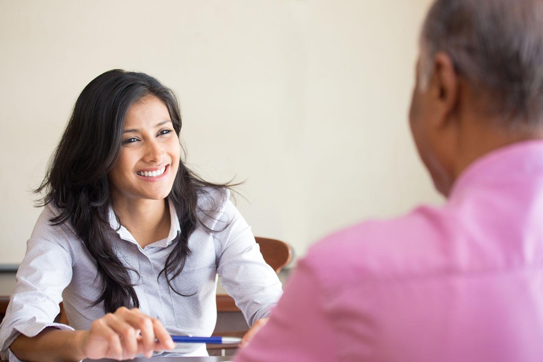 Mujer sonriente, con un bolígrafo entre las manos, conversa con un hombre
