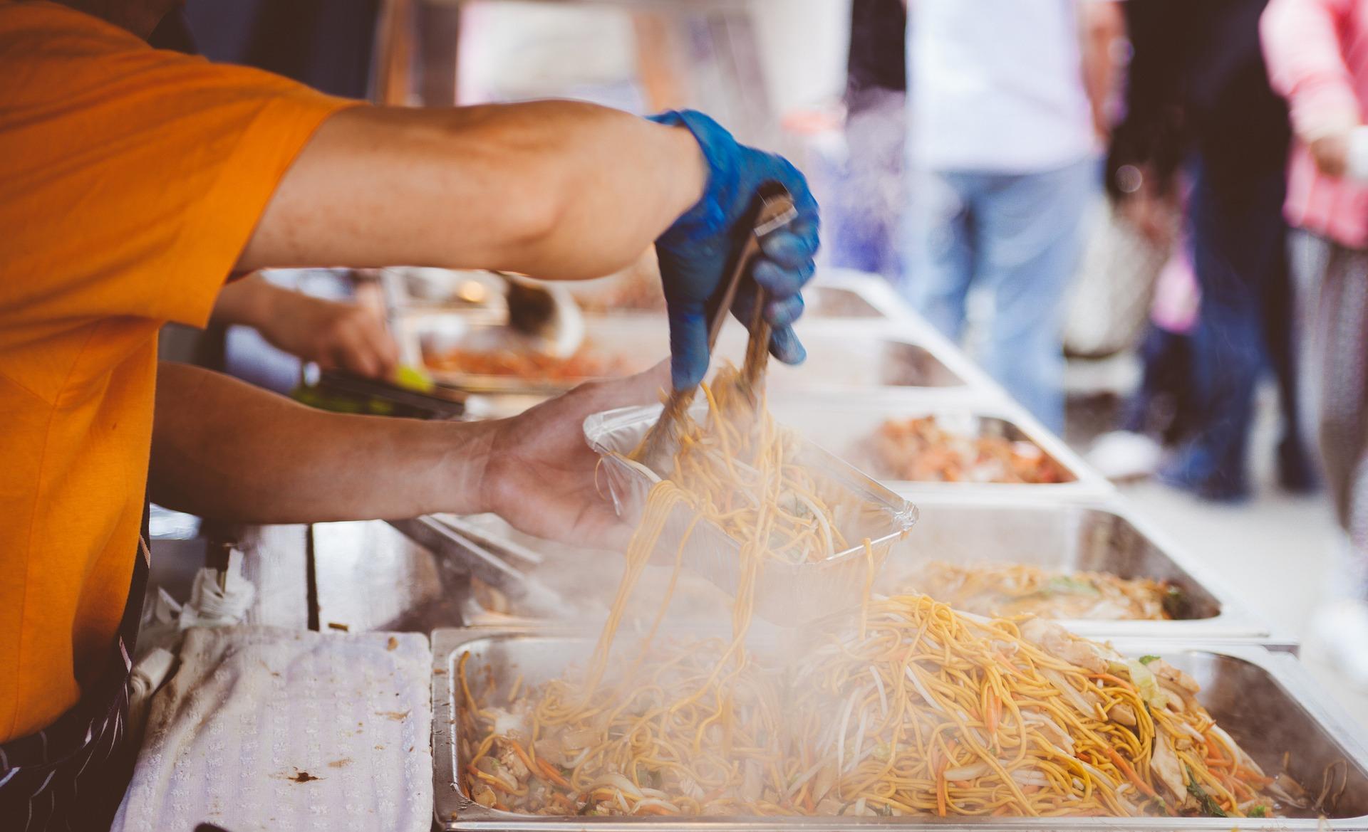 Manos de una persona sirviendo comida