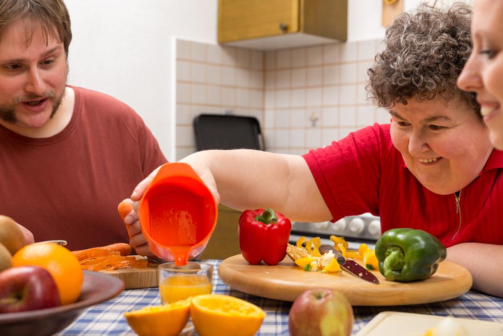 Mujer con discapacidad preparando un desayuno con zumo en un centro