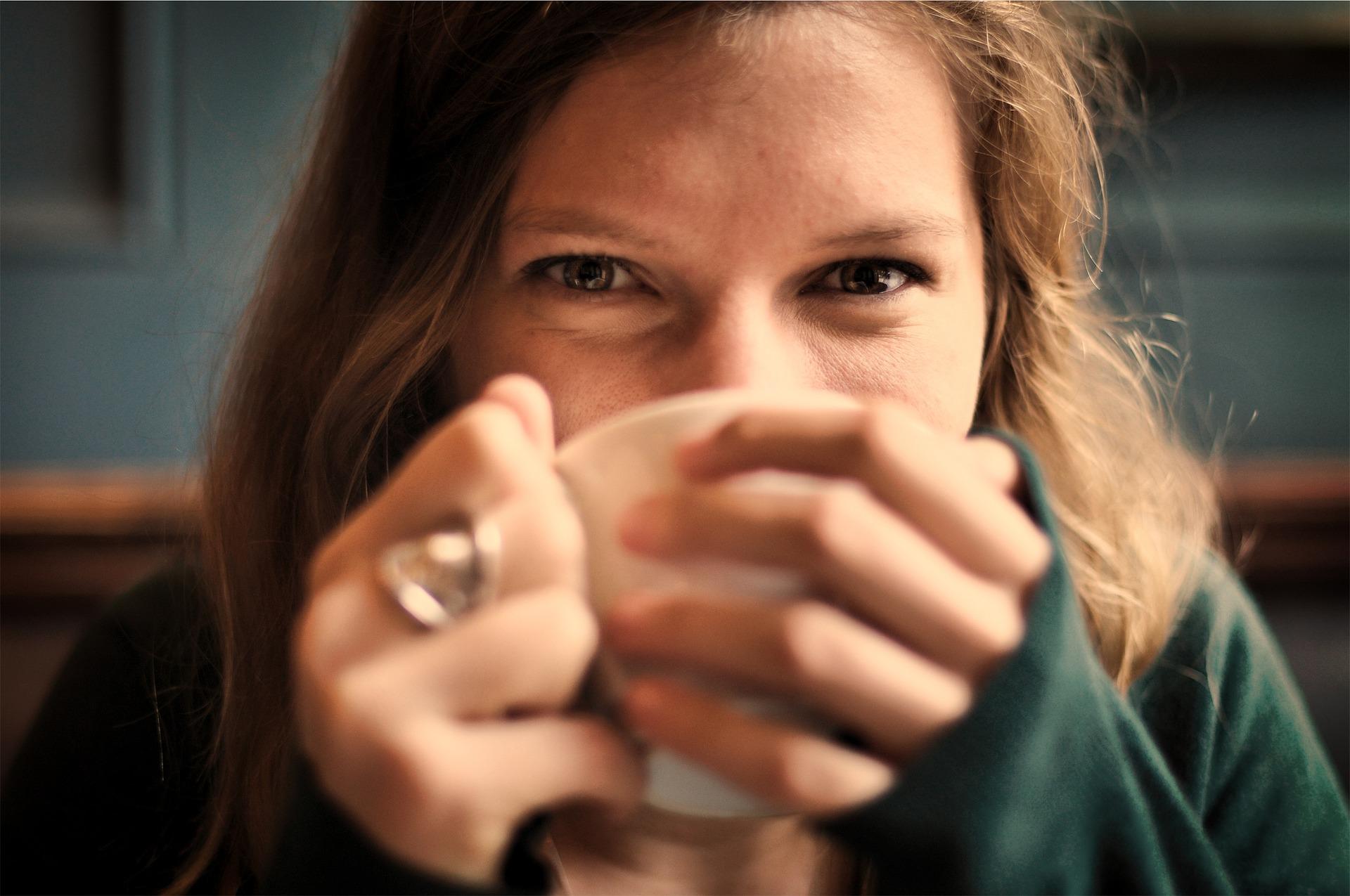 Chica joven bebiendo en una taza