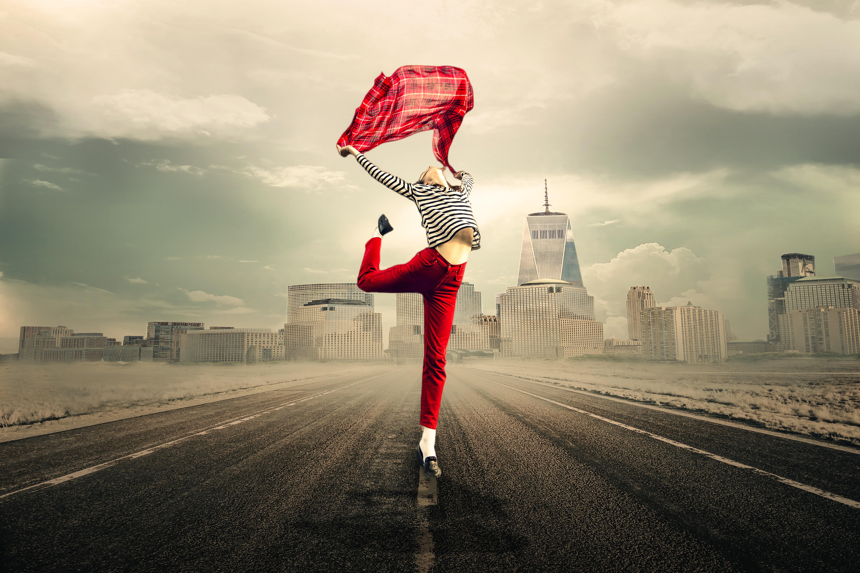 Chica saltando sobre una pierna levantando un pañuelo con los brazos