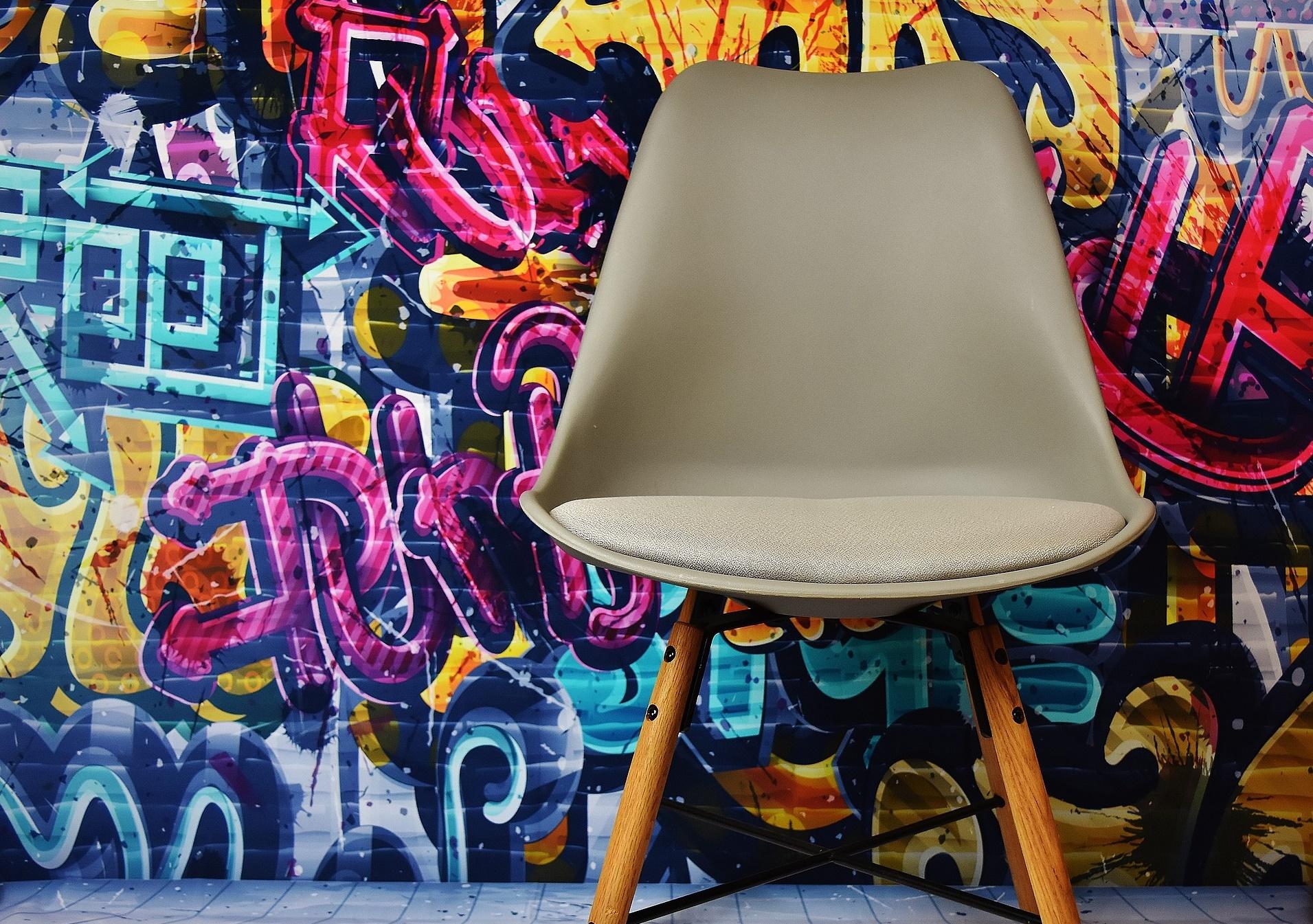 Silla vacía delante de pared con grafiti