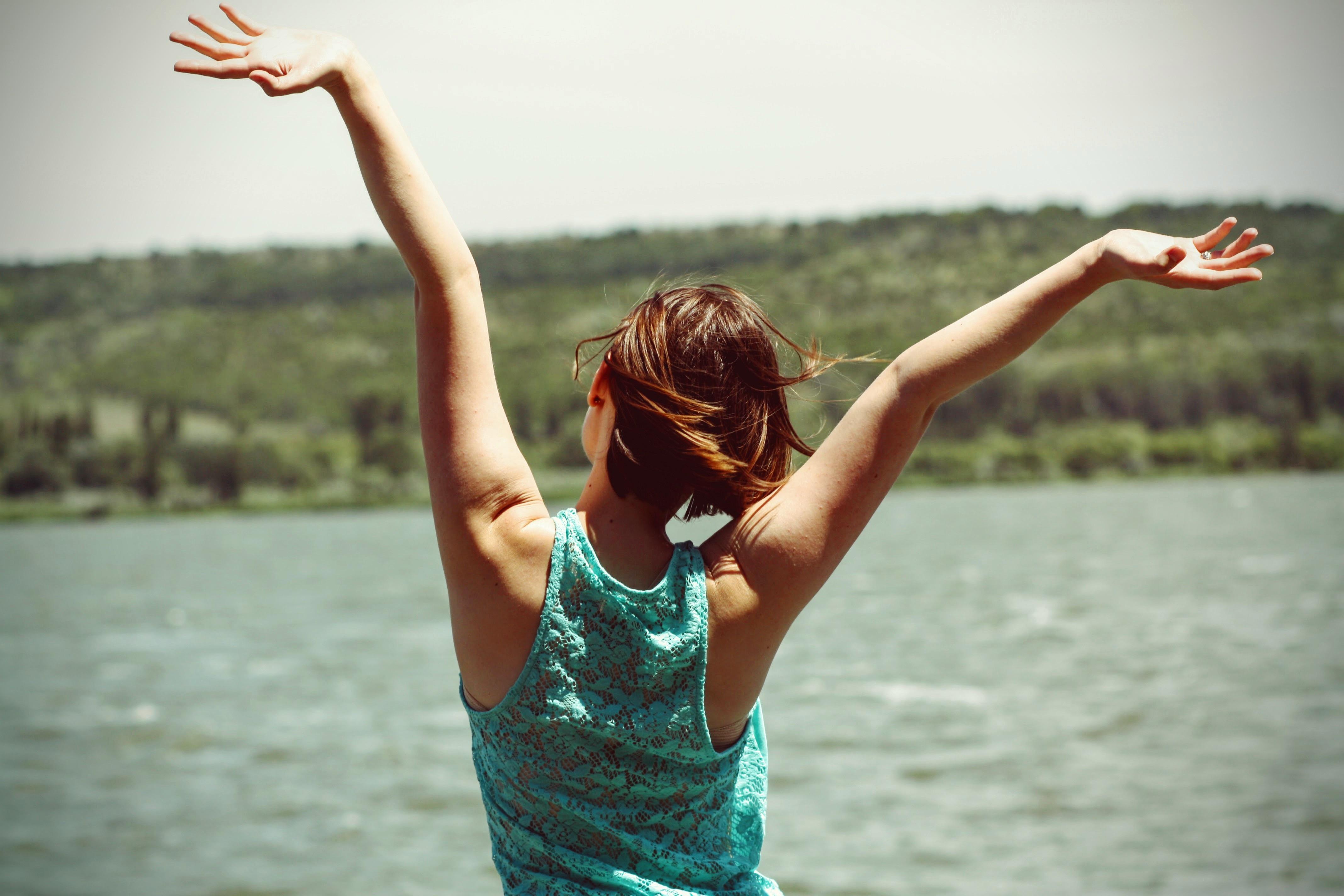 Joven de espaldas, brazos hacia arriba mirando a un lago