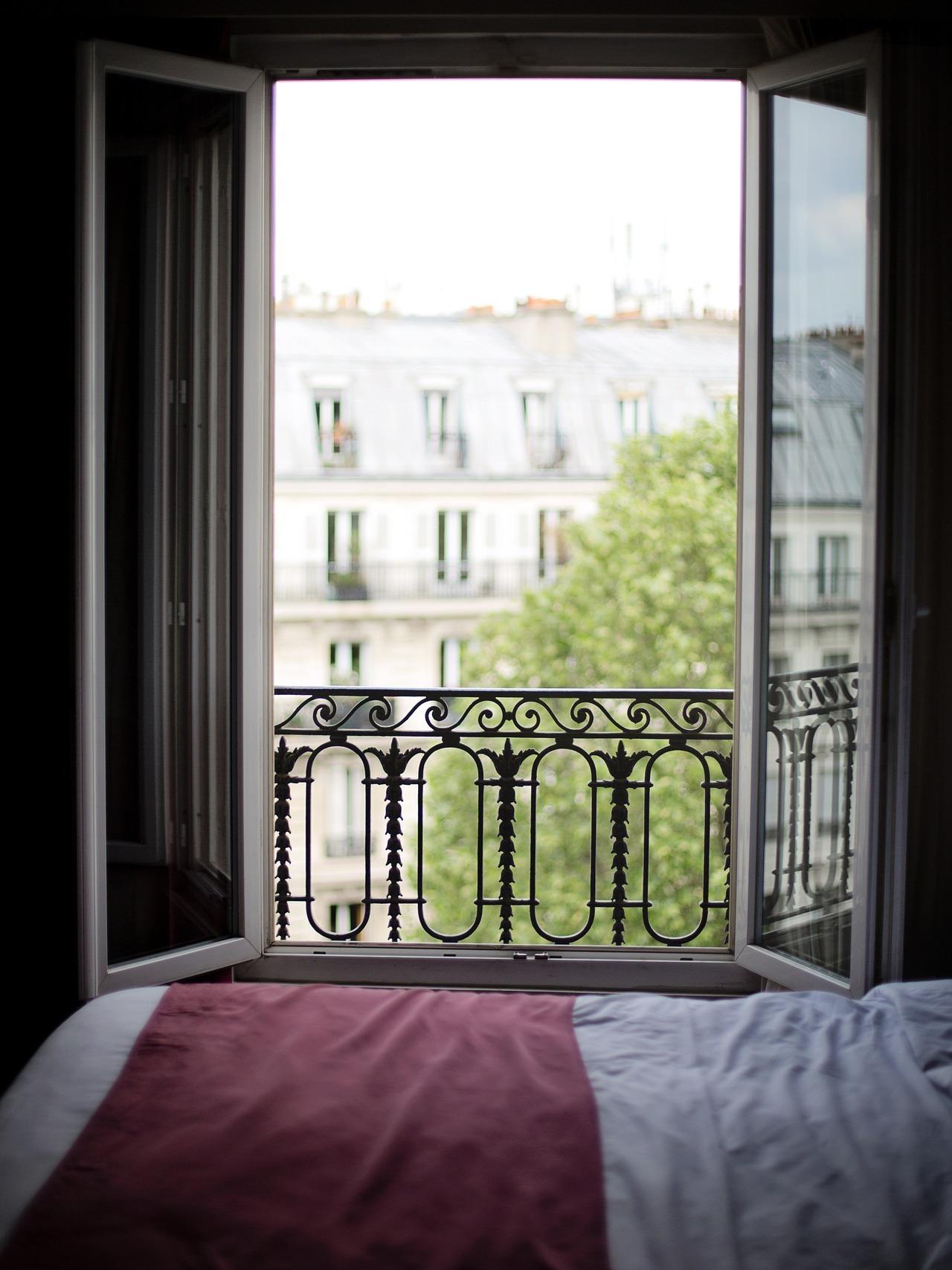 Imagen de la ventana abierta de un dormitorio en penumbra