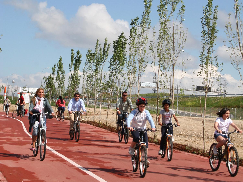 Imagen de ciclistas, adultos y niños, circulando por el carril bici del Anillo Ciclista