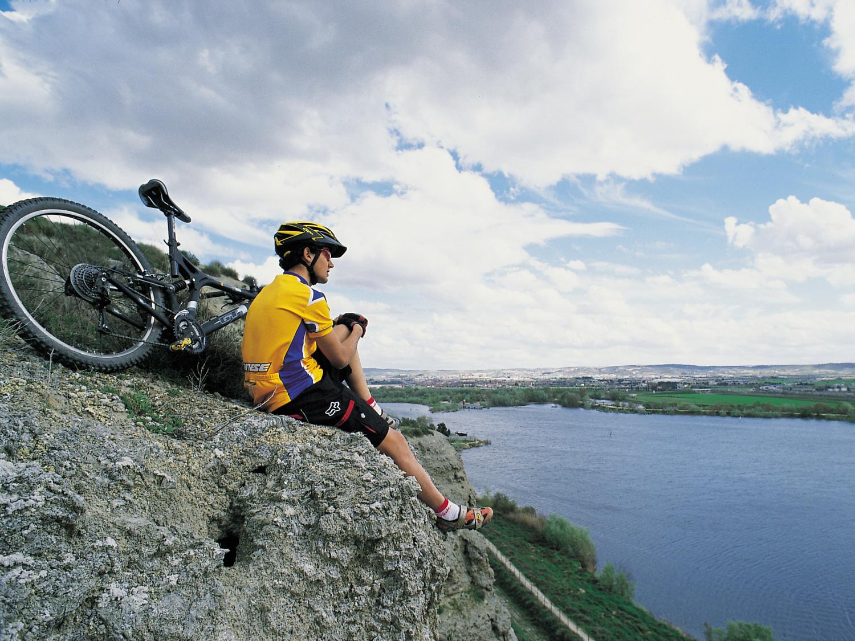 Ciclista sentado entre las rocas sobre la laguna de El Campillo