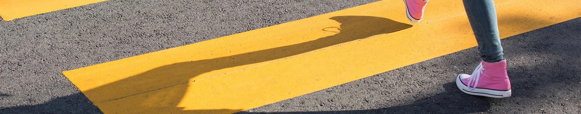 Paso de cebra amarillo en el que cruza una persona
