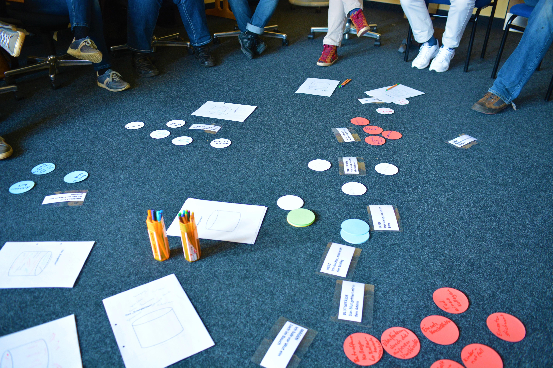 Notas y botes con bolígrafos sobre suelo de moqueta