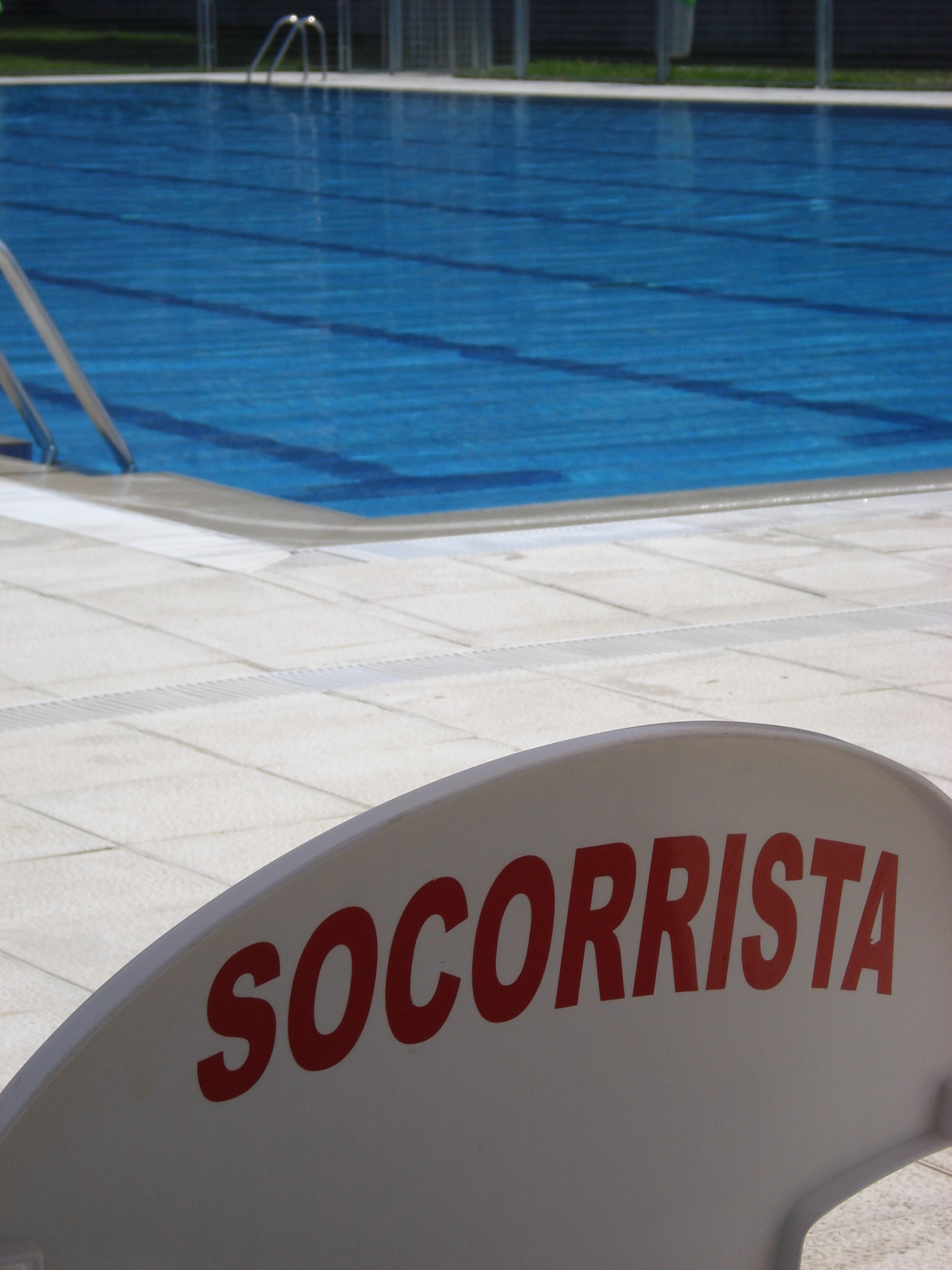 Imagen de la silla de un socorrista acuático en una piscina con el letrero Socorrista