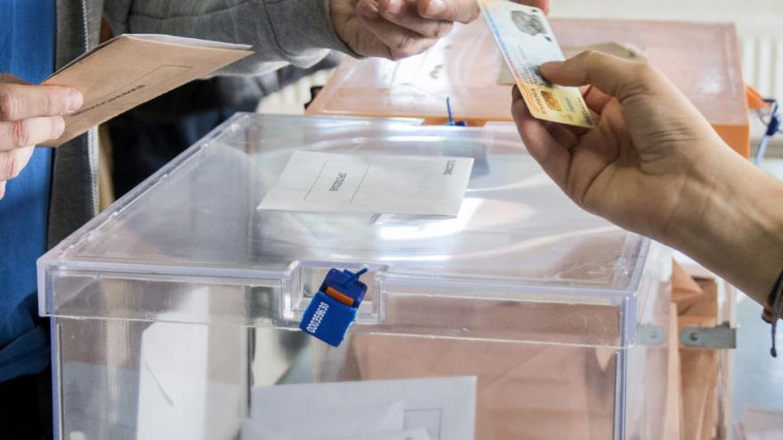 Hombre votando, da su dni por encima de la urna a la persona encargada de la mesa de votaciones