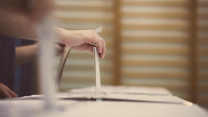 Una mano deposita la papeleta del voto en una urna electoral