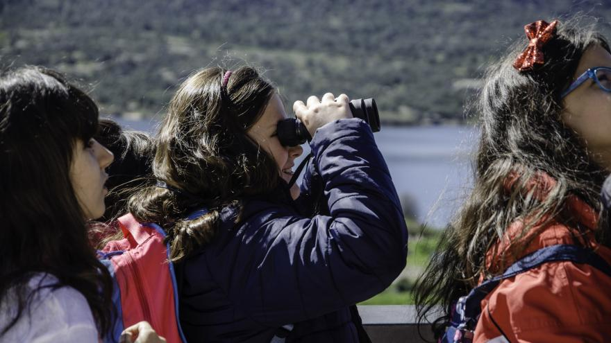Grupo de chicas mirando con unos prismáticos el paisaje de Manzanares