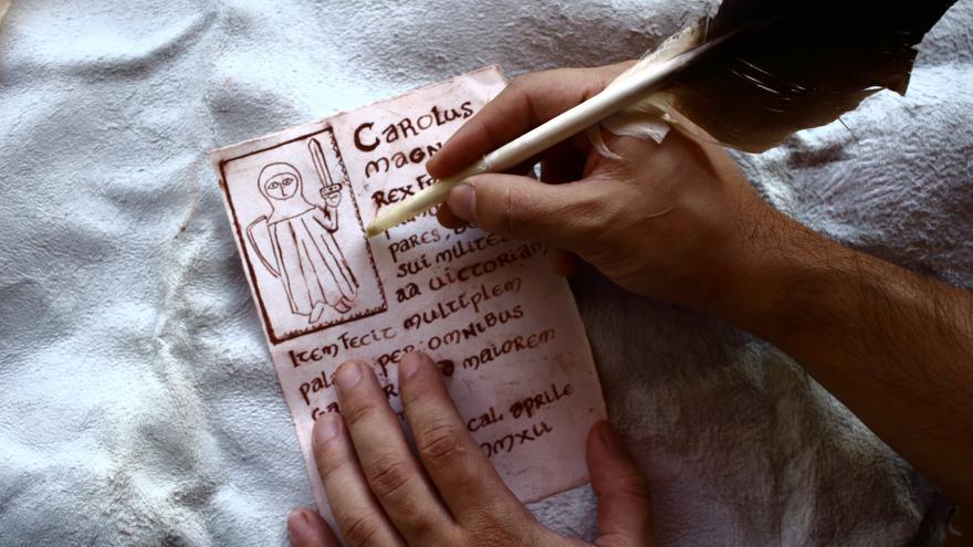 Manos escribiendo con una pluma sobre un papel a la manera antigua