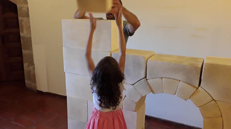 Hombre y niña jugando con bloques creando un arco y una torre arquitectónica