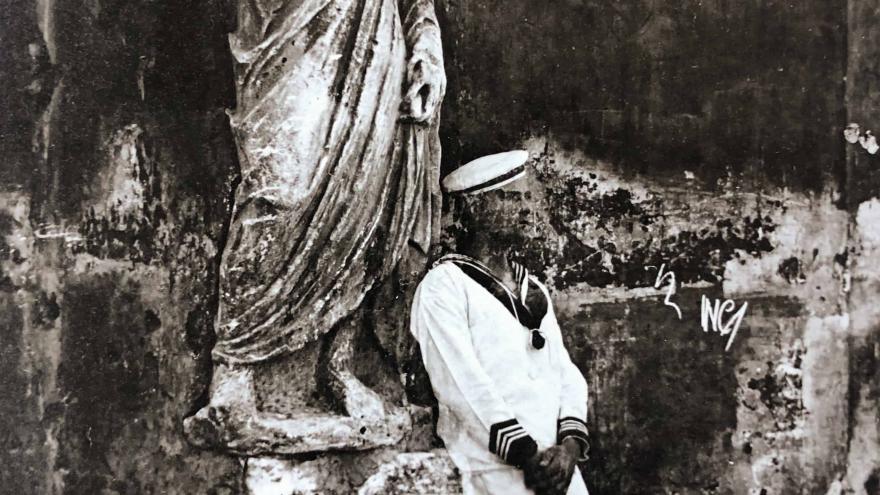 Marinero apoyado en una escultura clásica togada