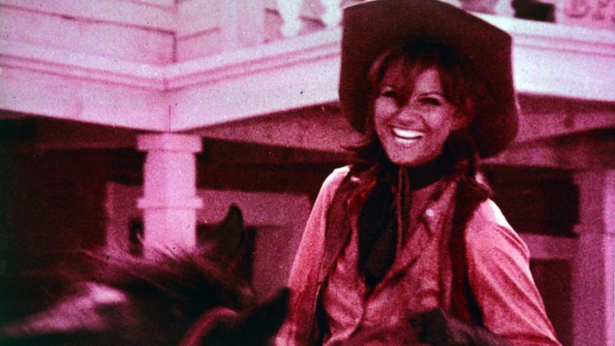 Mujer con sombrero vaquero montando a caballo