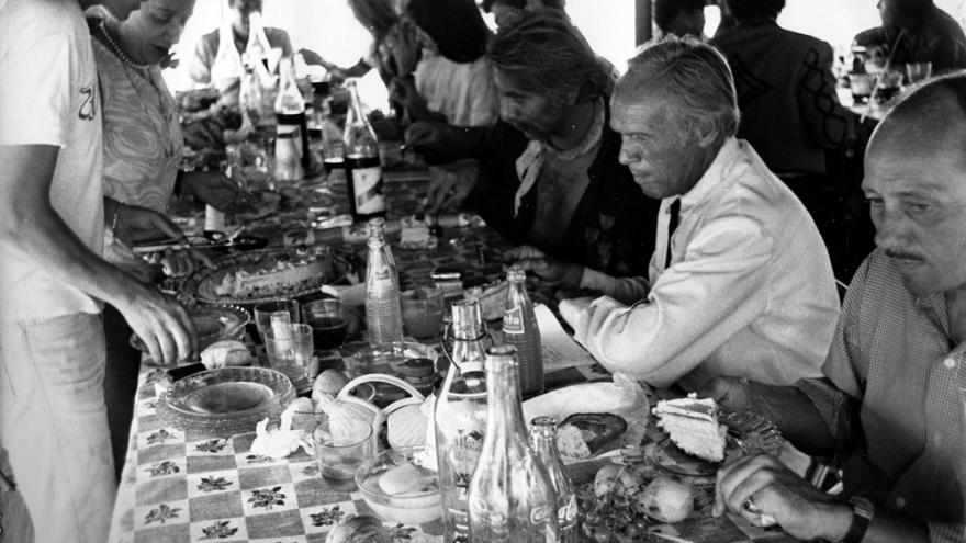 Varias personas, sentadas o de pie, comiendo alrededor de una mesa