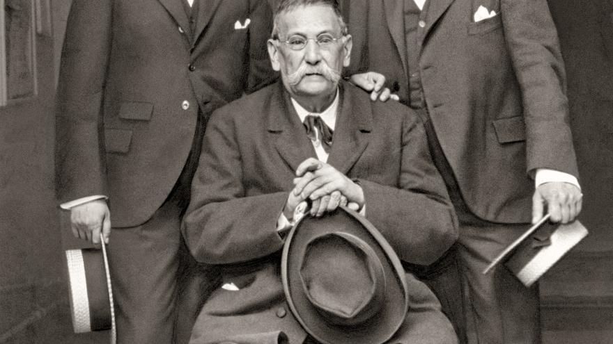 Galdós sentado, flanqueado por los hermanos Álvarez Quintero de pie