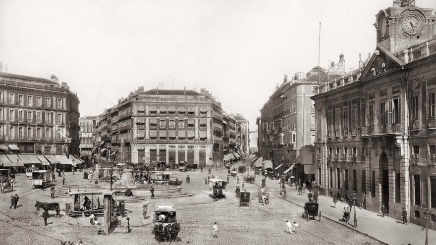 Puerta del Sol con peatones y carruajes de caballos