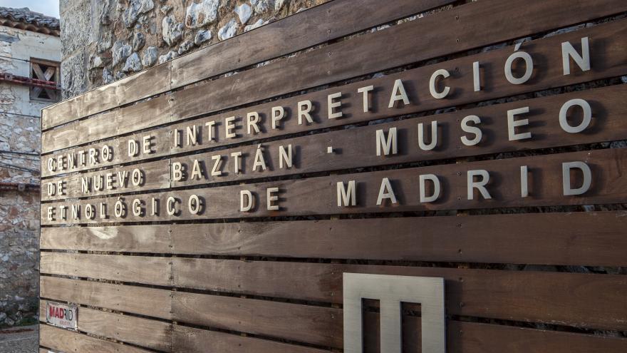 Panel de manera en la entrada al Centro de Interpretación de Nuevo Baztán con el nombre y logo del centro en color blanco