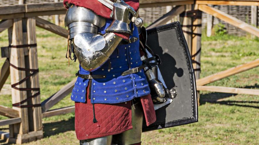 Caballero con armadura, escudo y espada al hombro