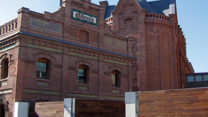 """Edificio de ladrillo rojo con azulejos con el nombre de la fábrica """"El Águila"""""""