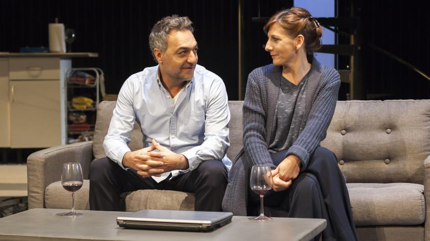 Una pareja sentada en un sofá con una copa de vino