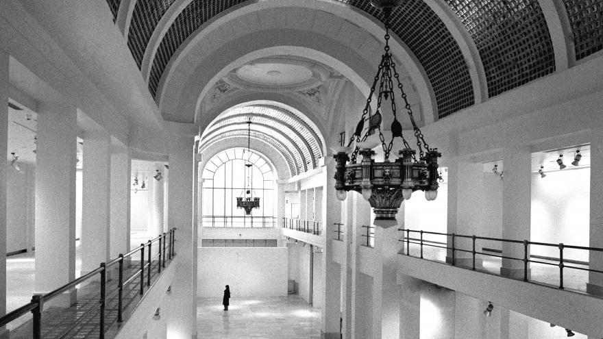 Vista en blanco y negro de la bóveda de cristal, lámpara y sala de exposiciones de la Consejería de Cultura