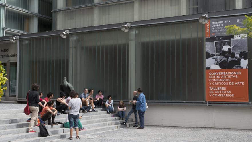 Patio de acceso a la Sala El Águila con un grupo de personas sentadas en las escaleras de pieza charlando