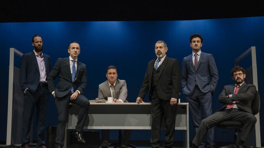 Seis chicos con caras serias sentados en una mesa
