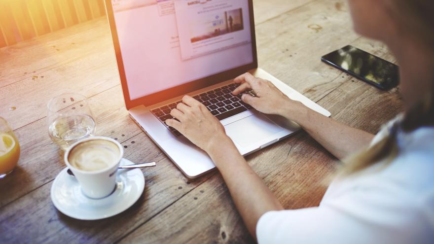 Persona sentada ante una mesa, tecleando en un portátil. A su derecha, hay un móvil; a su izquierda, una taza de café, un vaso de agua y otro de naranja
