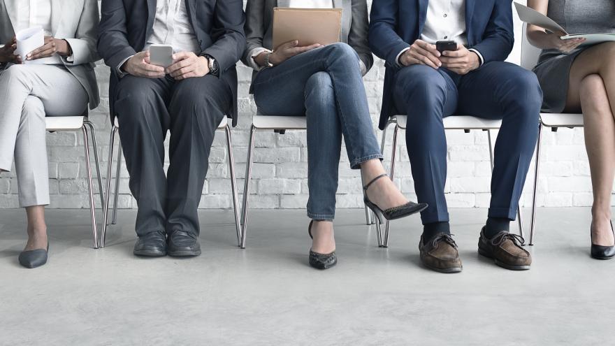 Cinco personas esperan sentadas a ser atendidas en un proceso de selección de personal. Los dos hombres están leyendo sus móviles, una mujer sujeta unos papeles y, las otras dos, sujetan carpetas