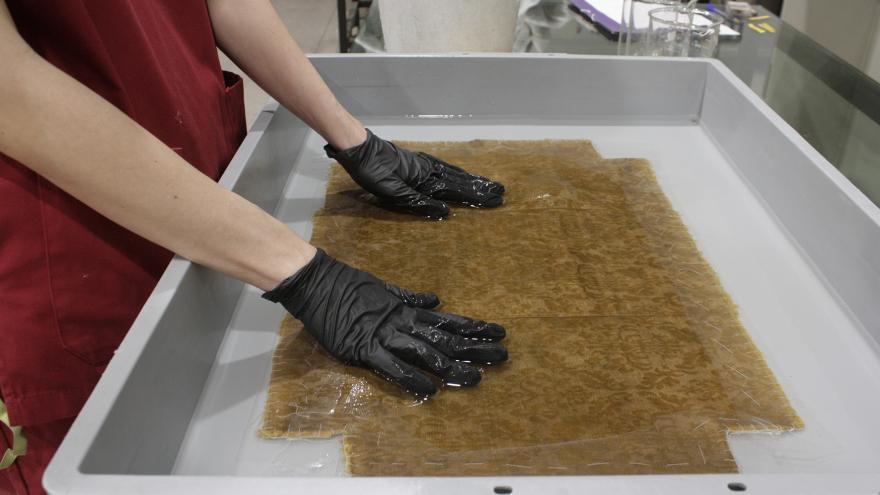 Manos limpiando en agua uno de los cojines restaurados