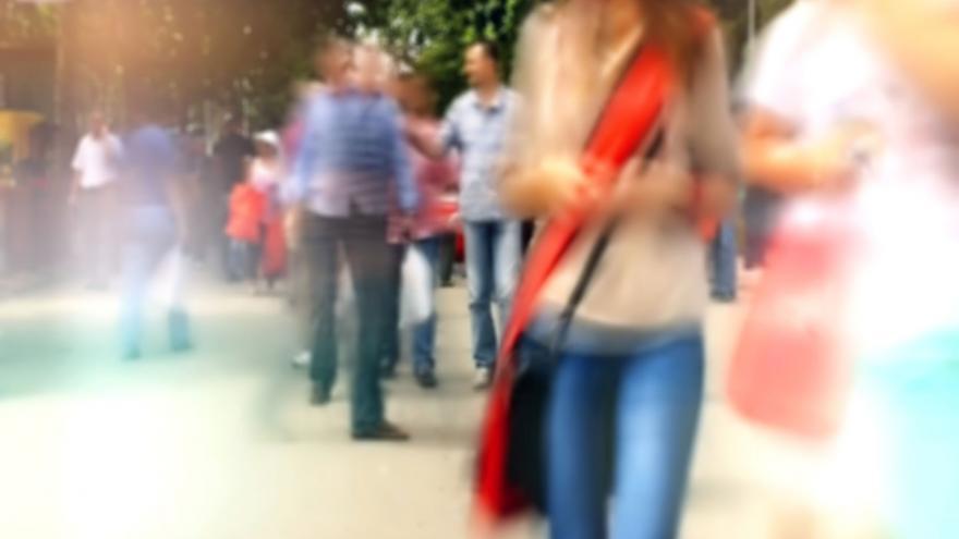 Joven en vaqueros paseando por la calle, con gente a su alrededor