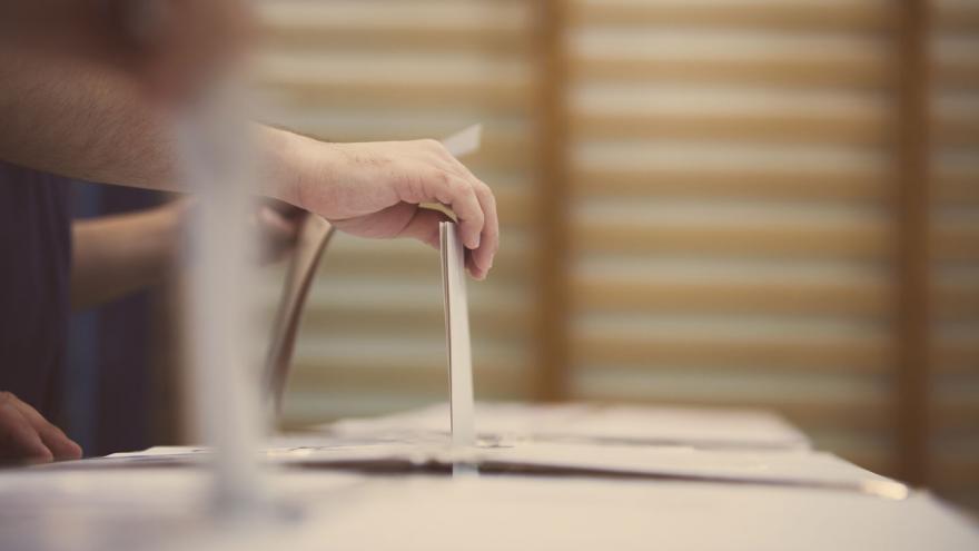 Una mano deposita unas papeletas en una urna de votación