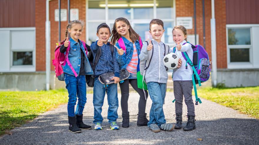 Cinco niños posando sonrientes con sus mochilas a la espalda