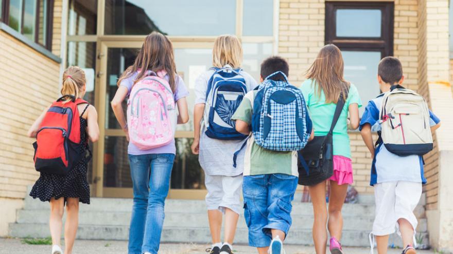 Colegiales con mochilas, de espaldas, a punto de entrar al colegio