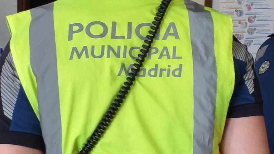 Policía visto por detrás con el chaleco amarillo que dice Policía Municipal de Madrid