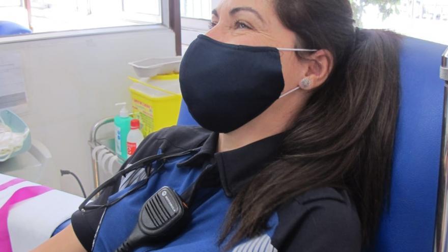 Policía mujer donando en una imagen de perfil izquierdo