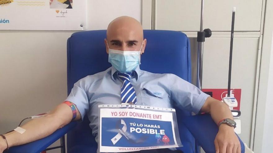 Trabajador de la EMT donando con un cartel de apoyo a la donación