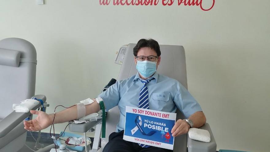 Trabajador de la EMT donando bajo un lema de la pared: Dona sangre de corazón
