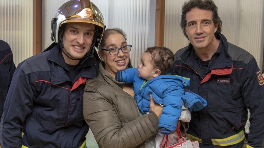 Bomberos del Parque de Getafe posan con madre y niña en Navidad