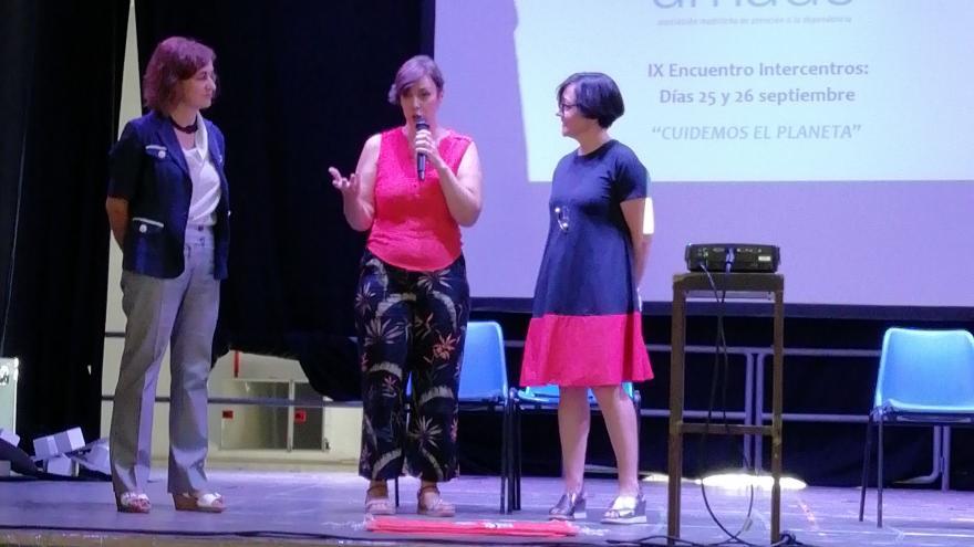 Mujer en un escenario presentando un acto