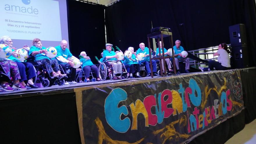 Personas mayores en sillas de ruedas en un escenario
