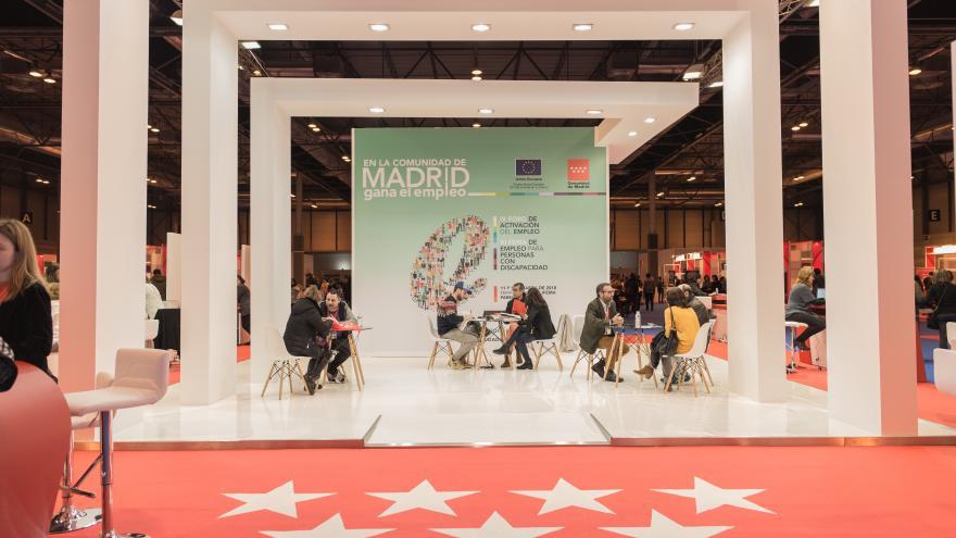 Stand de Comunidad de Madrid con personas ante mostrador y cartel conmemorativo de la edición 2018