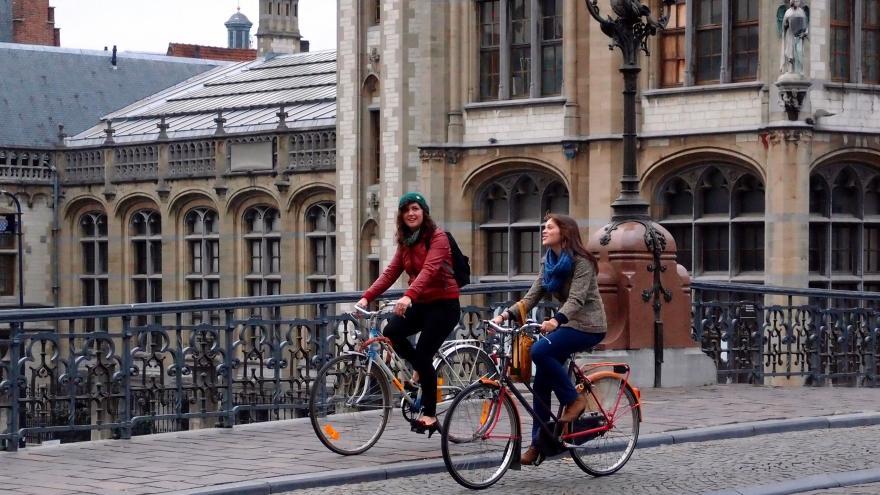 Dos chicas montando en bici por una ciudad