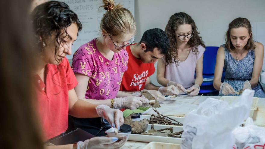 Grupo de jóvenes limpiando objetos arquológicos