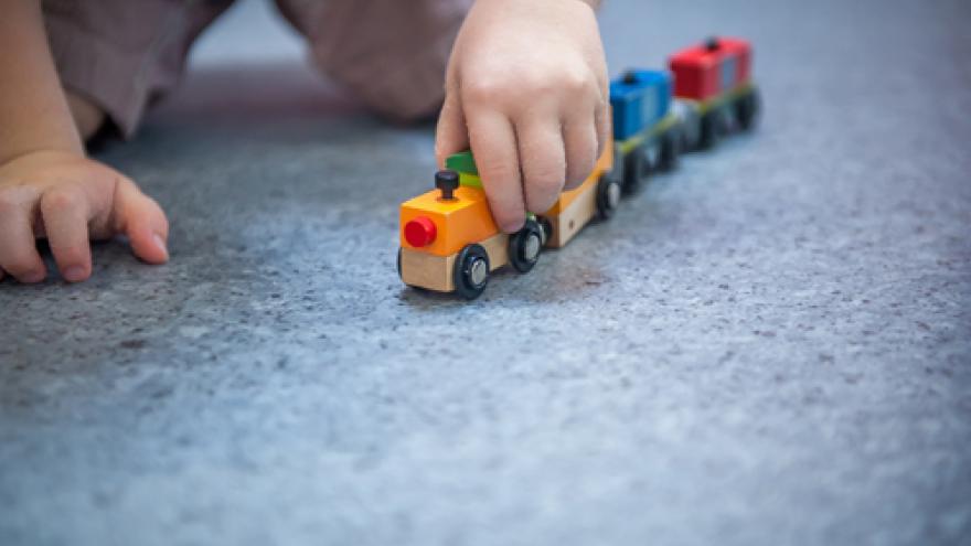 Bebé jugando con tren de madera