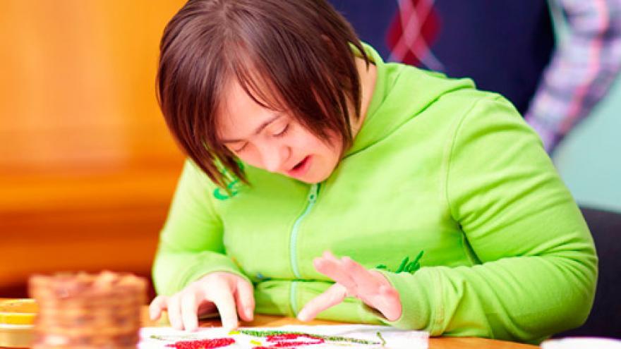 Joven con discapacidad intelectual realiza un trabajo de artesanía