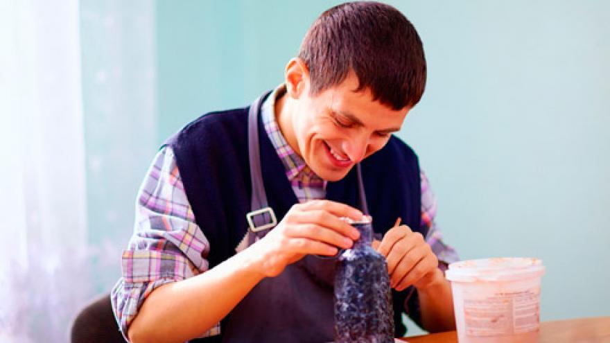 Joven con discapacidad intelectual trabajando en una pieza cerámica